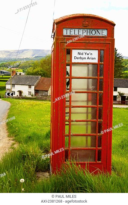 Phone booth with a sign saying coins not accepted in Welsh; Brecon Beacons, Wales