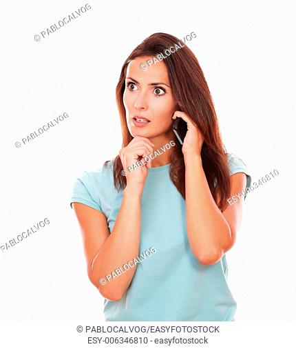 Portrait of reflective hispanic woman on blue t-shirt talking on her cell while looking to her right on isolated white background