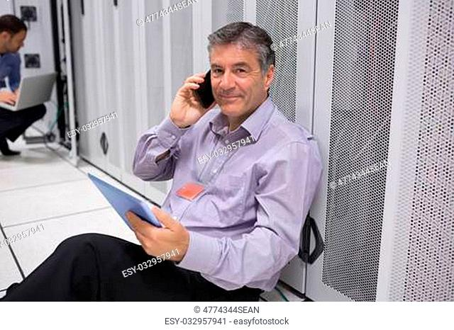 Technician phoning while working with his digital tablet and sitting on floor of data server