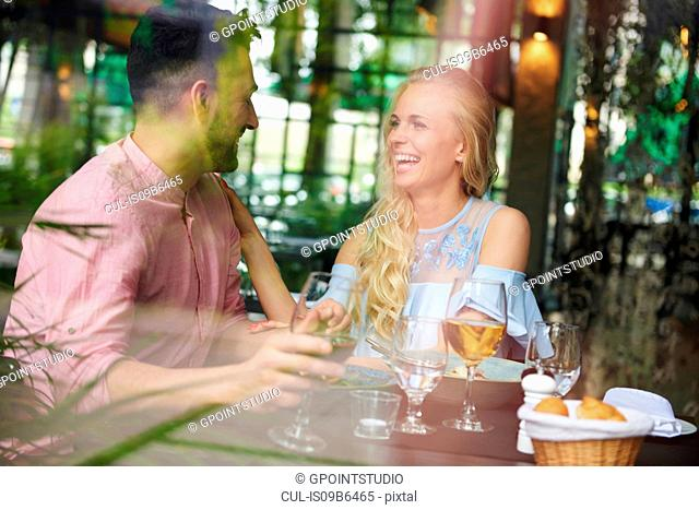 Window view of young woman with boyfriend laughing at restaurant table