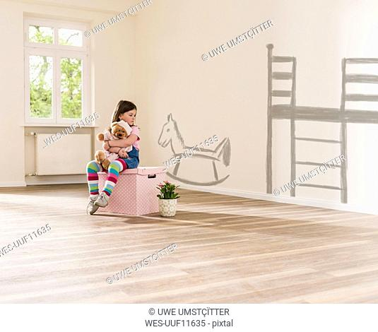 Girl in empty apartment sitting on a box holding teddy