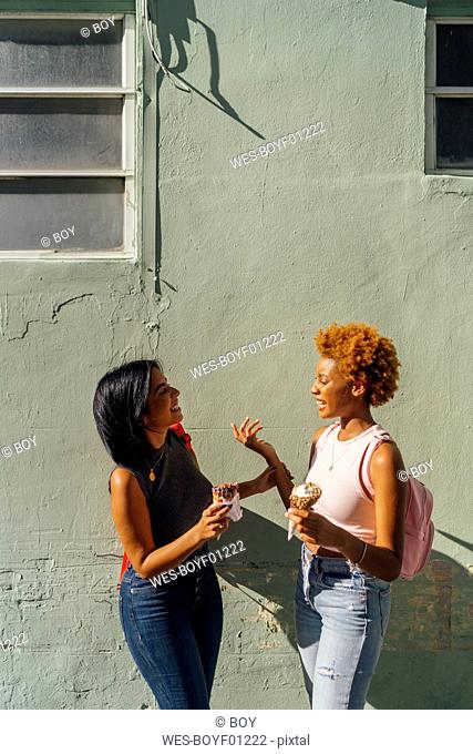 Two happy female friends with ice cream cones talking at a house wall