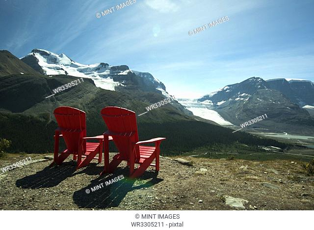 Red lawn chairs overlooking scenic mountain landscape