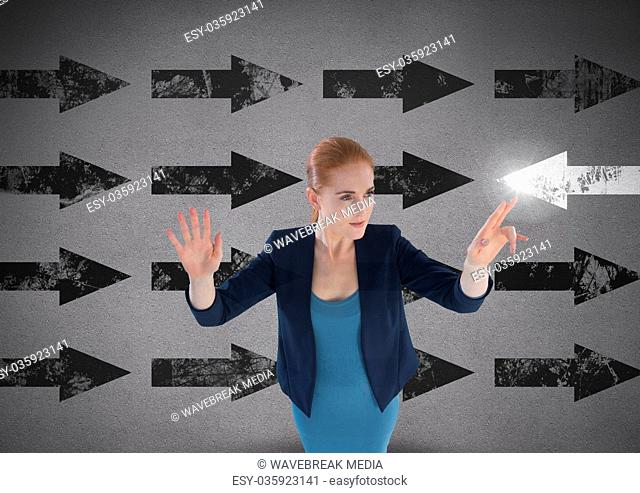 Businesswoman touching glowing arrow in opposite direction