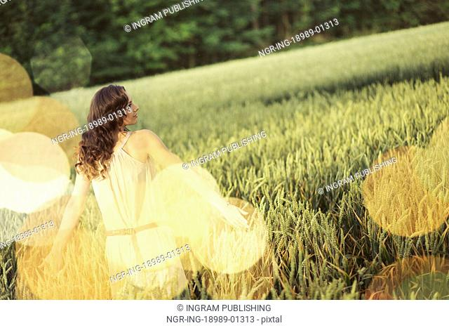 Vacation picture of the young woman among the corn crop