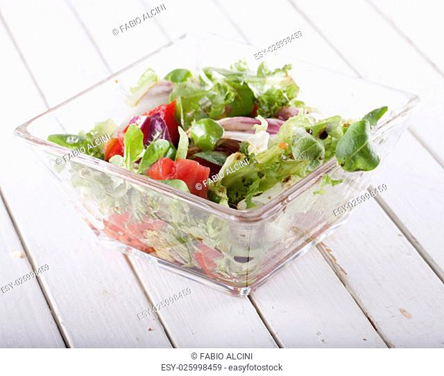 Salad over white wooden table, horizontal image