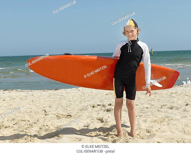 Portrait of confident boy nipper (child surf life savers) carrying surfboard, Altona, Melbourne, Australia