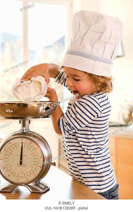 Young boy pouring flour onto scale