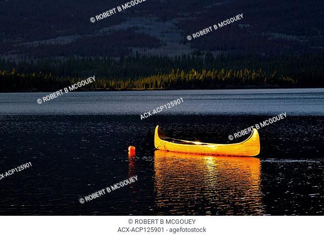 A cedar strip canoe in evening light on a calm lake in Jasper National Park Alberta Canada