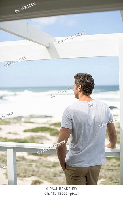 Man looking at ocean view from balcony