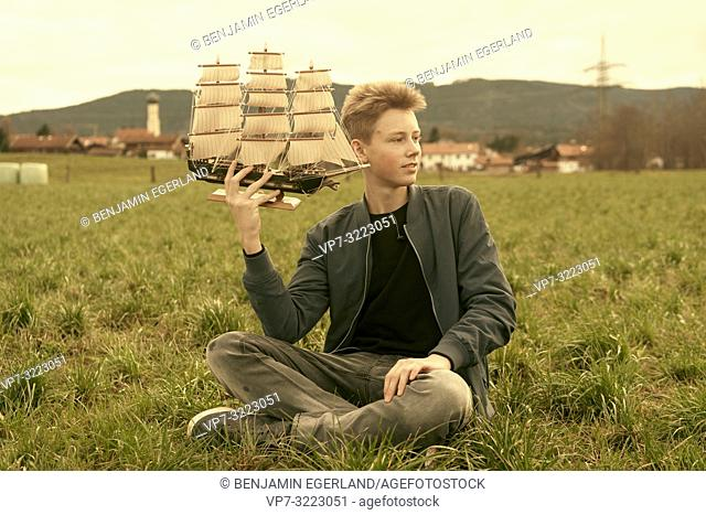 male teenager holding ship while sitting outdoors on meadow at countryside, travel lust, pensive mood, in Waakirchen, Bavaria, Germany