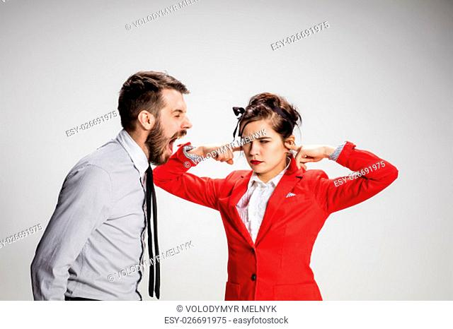 The funny business man and woman communicating on a gray background. Business concept relationship of colleagues