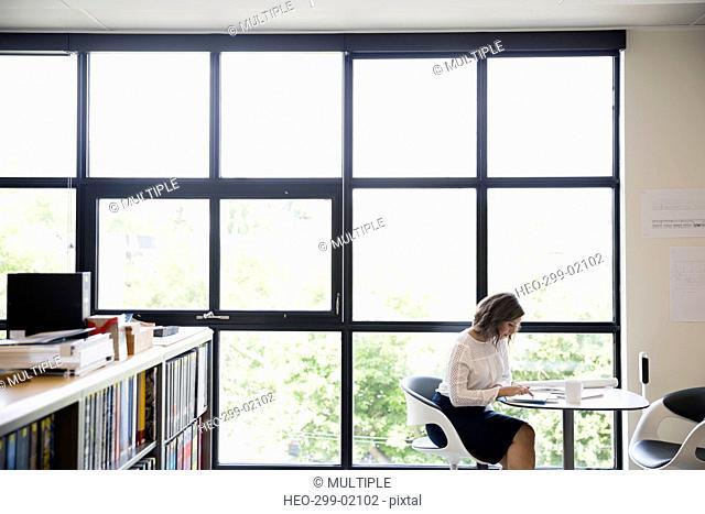 Female designer using digital tablet at office window