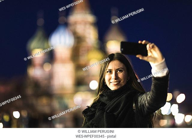 Russia, Moscow, young woman taking a selfie at Red Square with St Basil's cathedral in background