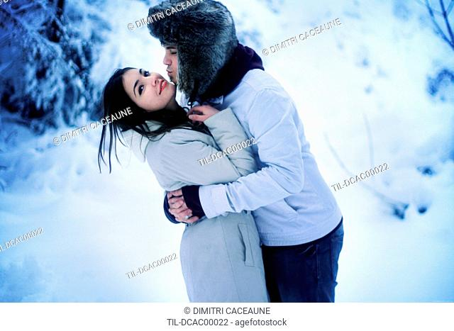 Young adult couple in winter embrace outdoors in snow