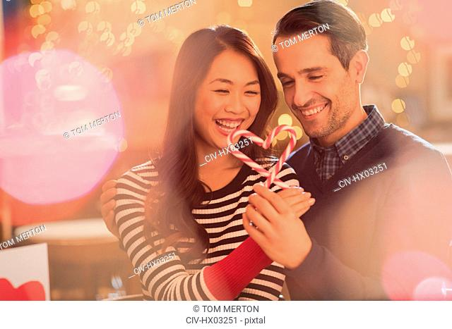 Couple holding heart-shape candy canes