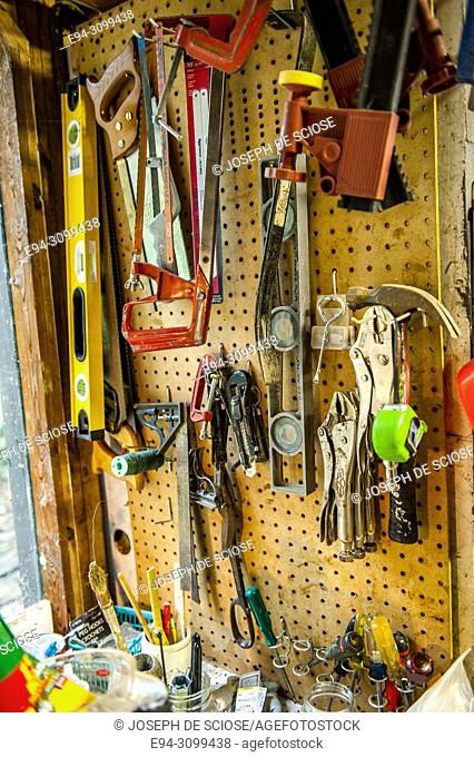 The inside of a storage shed filled with various tools and garden implements
