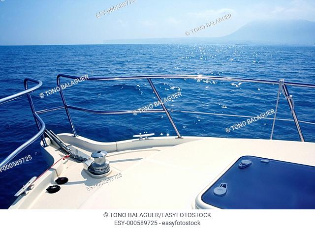 boat bow sailing on blue sea with anchor chain and winch detail