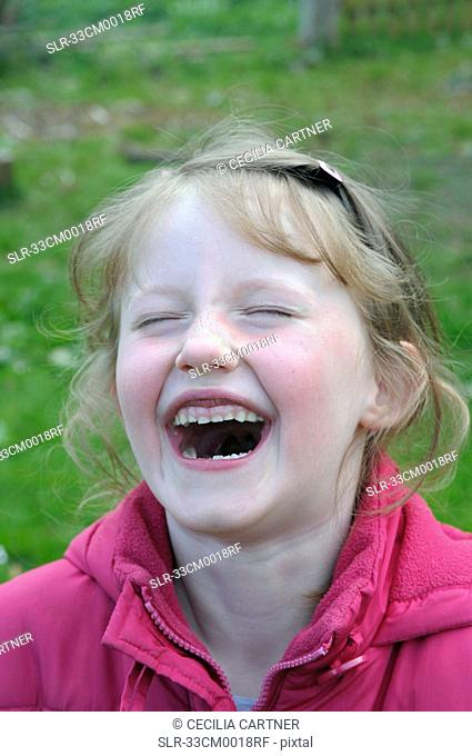 Close up of girl laughing in backyard