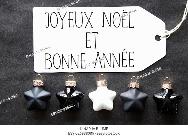 Label With French Text Joyeux Noel Et Bonne Annee Means Merry Christmas And Happy New Year. Black And White Christmas Tree Balls On Black Paper Background