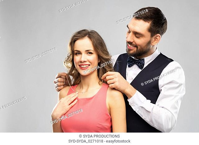 happy man puts necklace on his girlfriend