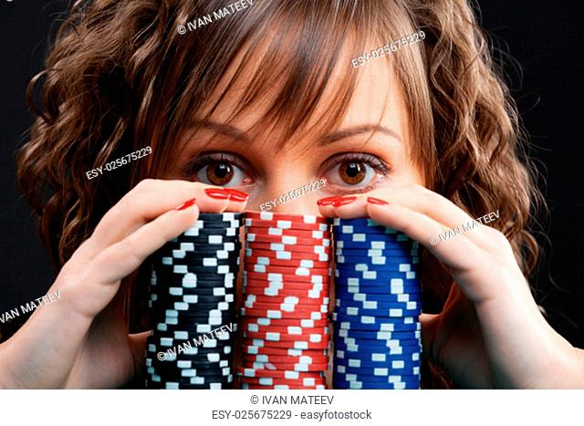 Young woman with gambling chips on black background