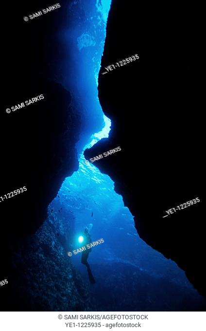 France marseille arc en ciel cave scuba diver shining a flashlight underwater
