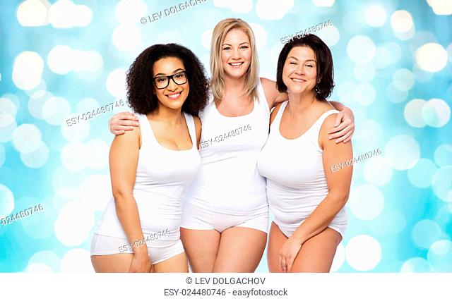 friendship, beauty, body positive and people concept - group of happy plus size women in white underwear over blue holidays lights background