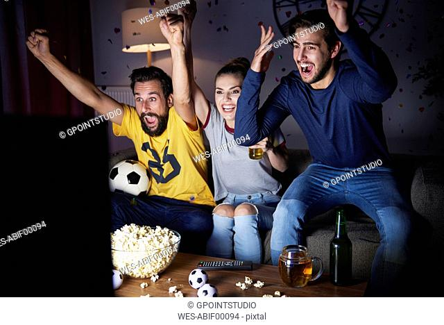 Excited friends sitting on the sofa watching Tv