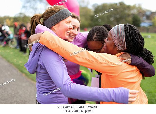 Happy female runners hugging at charity run finish line, celebrating