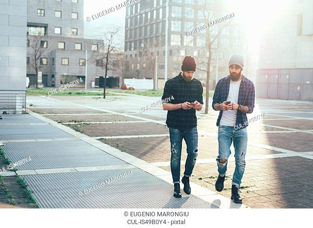 Two young male hipsters walking in city while looking at smartphones