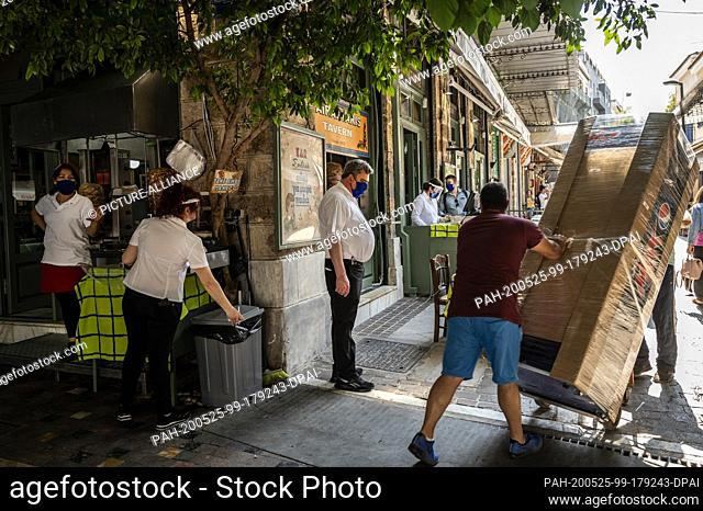 25 May 2020, Greece, Athen: Waiters are standing in front of a restaurant about to reopen. Greece relaxes measures imposed because of the Corona pandemic
