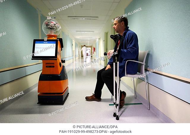 29 October 2019, Thuringia, Eisenberg: Matthias Porsch, patient, with the help of Ringo, a robot, trains walking on a corridor in the hospital Waldkliniken...