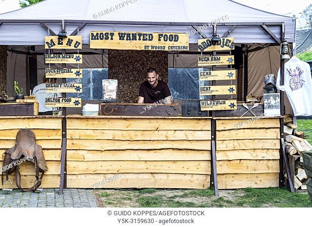 Tilburg, Netherlands. Adult, caucasian male standing inside his Western Style food stand, waiting for customers during the annual food truck festival