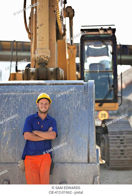 Worker standing by digger on site