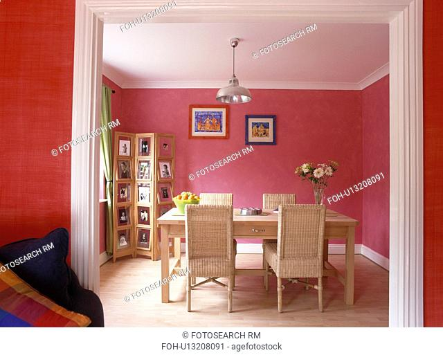 Wicker chairs and folding screen displaying photographs in modern pink dining room