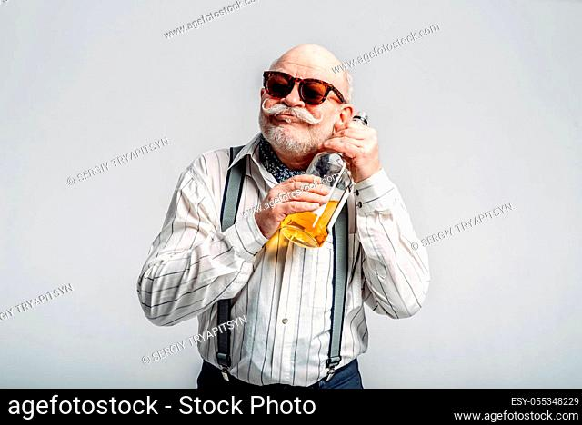 Fashionable elderly man hugs the bottle of good alcohol, grey background. Mature senior looking at camera in studio, dude