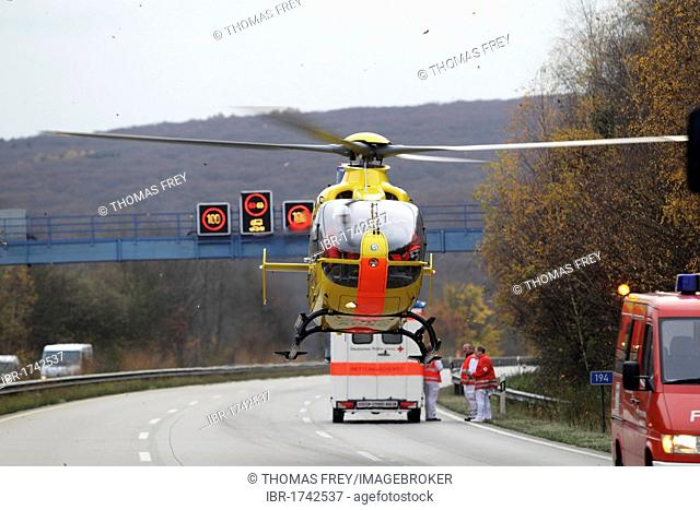 An ADAC EC 135 rescue helicopter taking-off at an accident site on the A61 motorway near Niederzissen, Rhineland-Palatinate, Germany, Europe