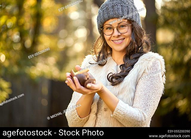 beautiful woman in cap and glasses is holding mushrooms in hands in autumn forest