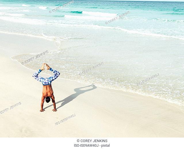Mature man doing handstand on beach, South Pointe Park, South Beach, Miami, Florida, USA