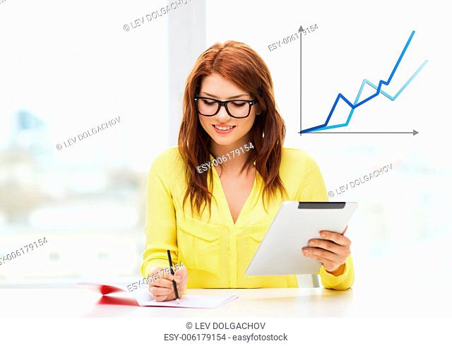 business, education and technology concept - smiling student in eyeglasses with tablet pc computer and notebook in college