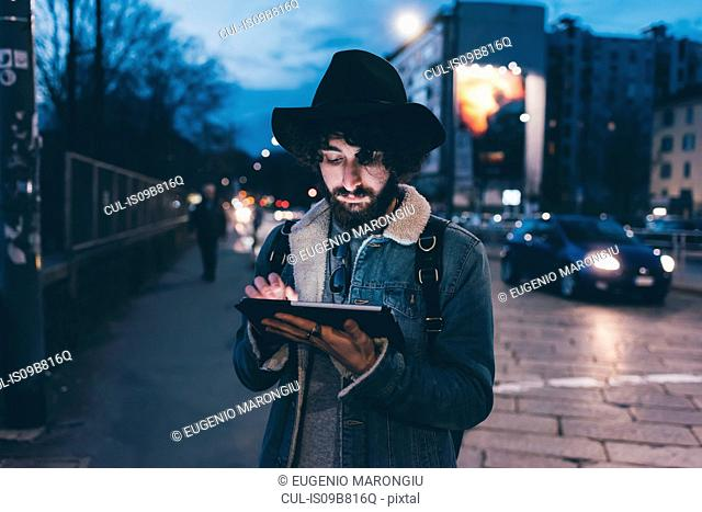 Young man standing in street at dusk, using digital tablet