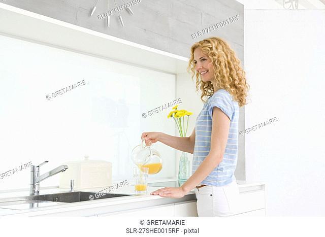 Woman pouring orange juice