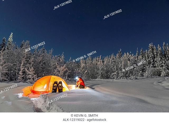 Man with headlamp sits by a lit tent near an evergreen and snow covered forest, Gakona, Southcentral Alaska, Winter