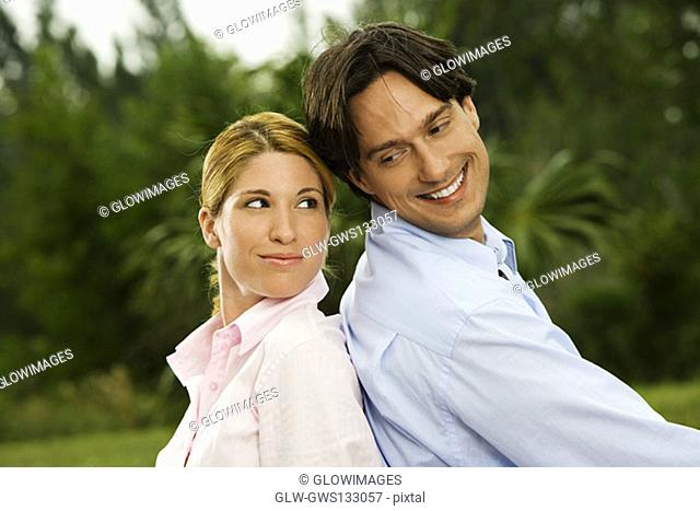 Side profile of a businessman and a businesswoman sitting back to back in the park