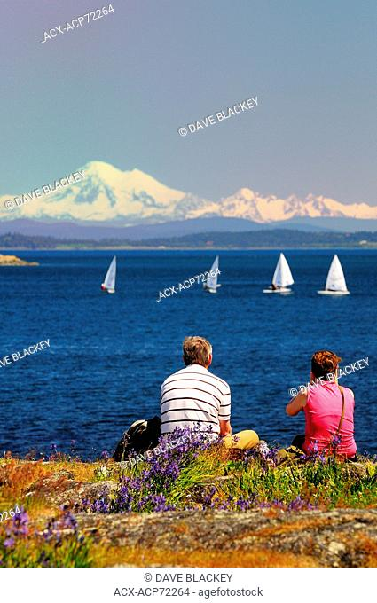 A couple watch laser sailboats racing off Cattle Point in Oak Bay in Victoria, BC