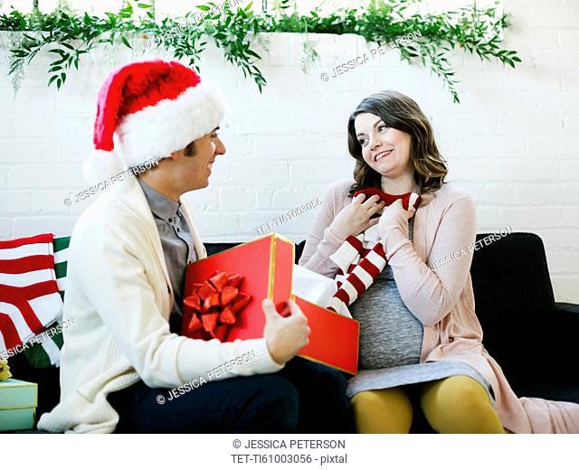 Pregnant woman receiving christmas present
