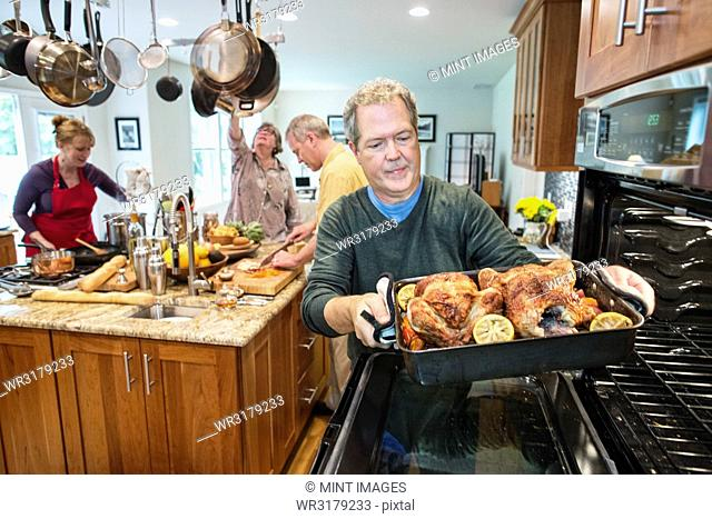 Senior man pull roast chickens out of the oven at a home dinner party