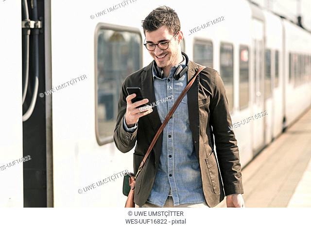 Smiling young man with cell phone at station platform