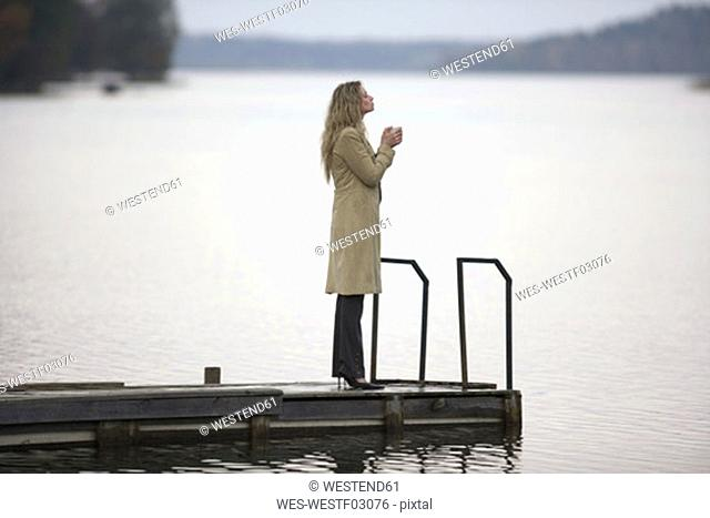 usinesswoman standing on jetty, holding cup, side view